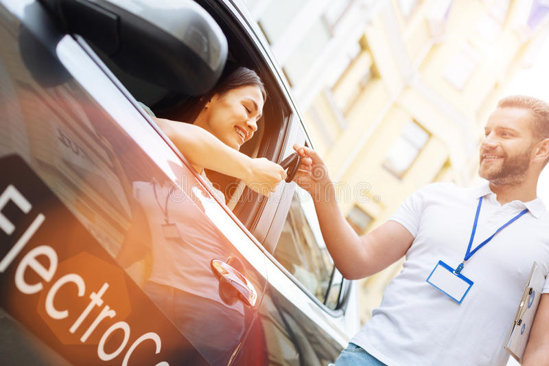 Lycklig ung kvinna som får hennes nya biltangenter royaltyfri foto