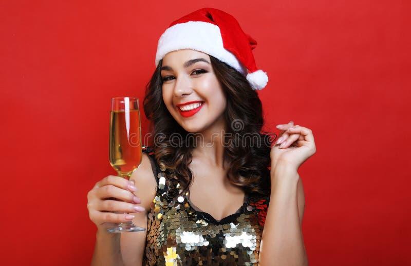 Lycklig ung kvinna som firar nytt ?r Den attraktiva le damen i jultomten cap att dricka champagne fotografering för bildbyråer
