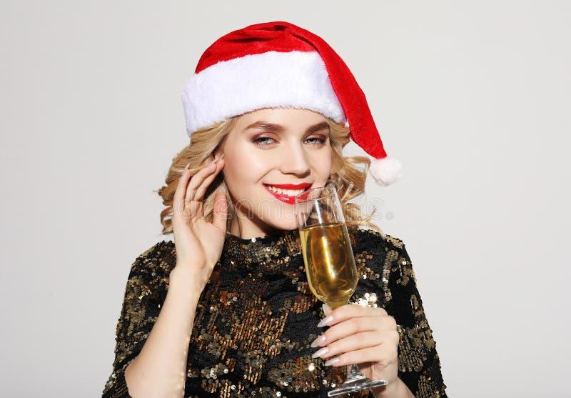 Lycklig ung kvinna som firar nytt ?r Den attraktiva le damen i jultomten cap att dricka champagne royaltyfria bilder