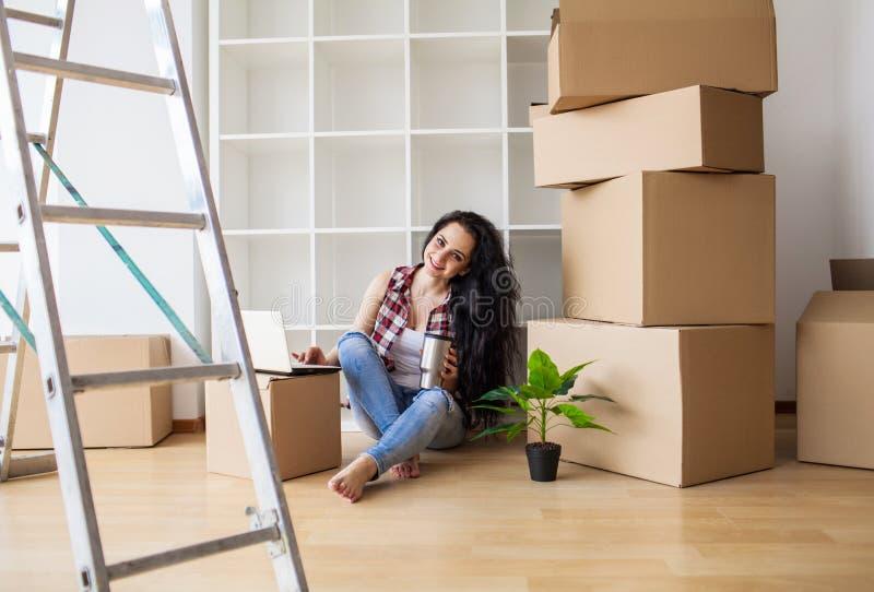 Lycklig ung kvinna som flyttar sig till det nya hemmet - ha gyckel arkivfoton