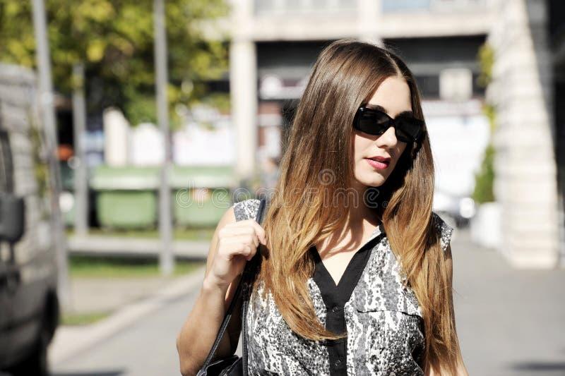 Lycklig ung kvinna som går och shoppar i stad Moderiktig kvinnakonsument som ser shoppafönstren royaltyfria foton