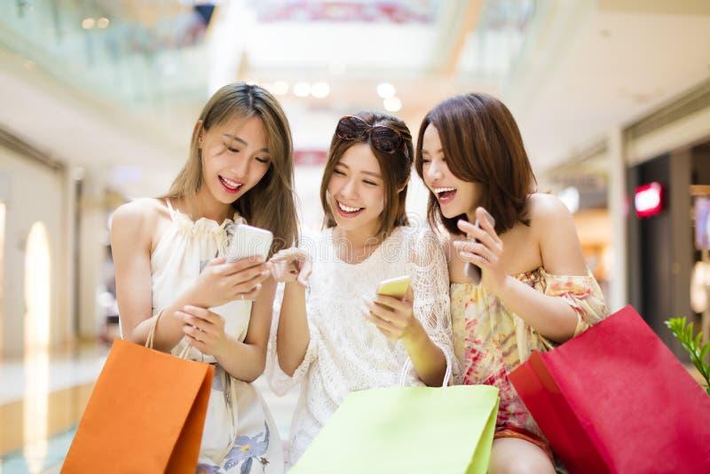 Lycklig ung kvinna som håller ögonen på den smarta telefonen i shoppinggalleria royaltyfri bild
