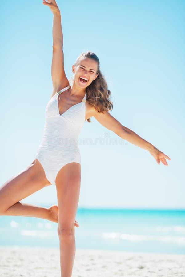 Lycklig ung kvinna som har gyckel på stranden arkivfoto