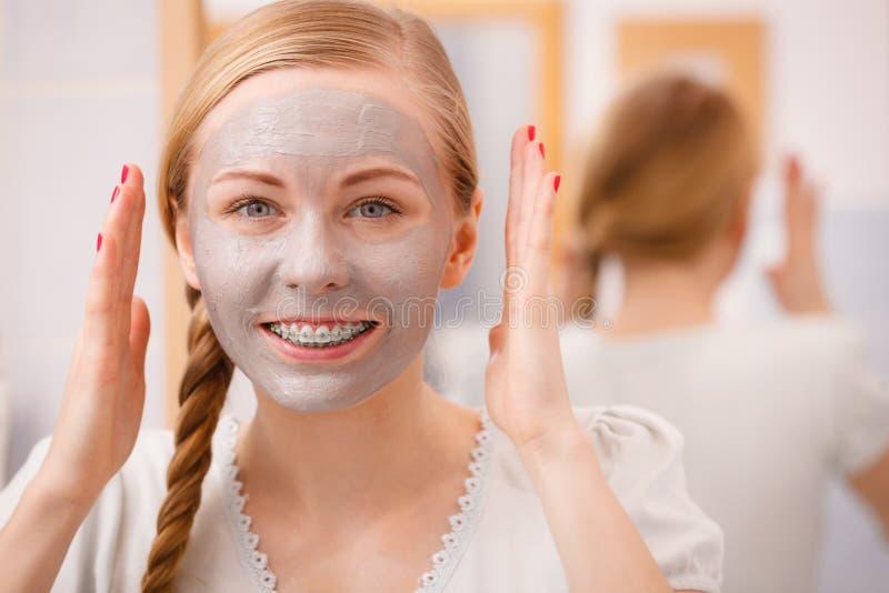 Lycklig ung kvinna som har gyttjamaskeringen på framsida royaltyfria bilder