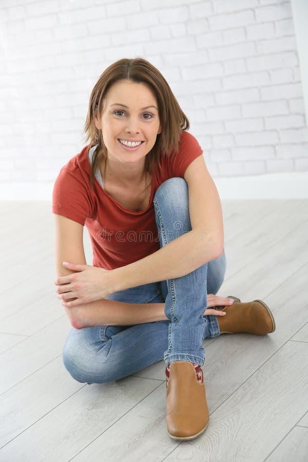 Lycklig ung kvinna som hemma sitter arkivfoton