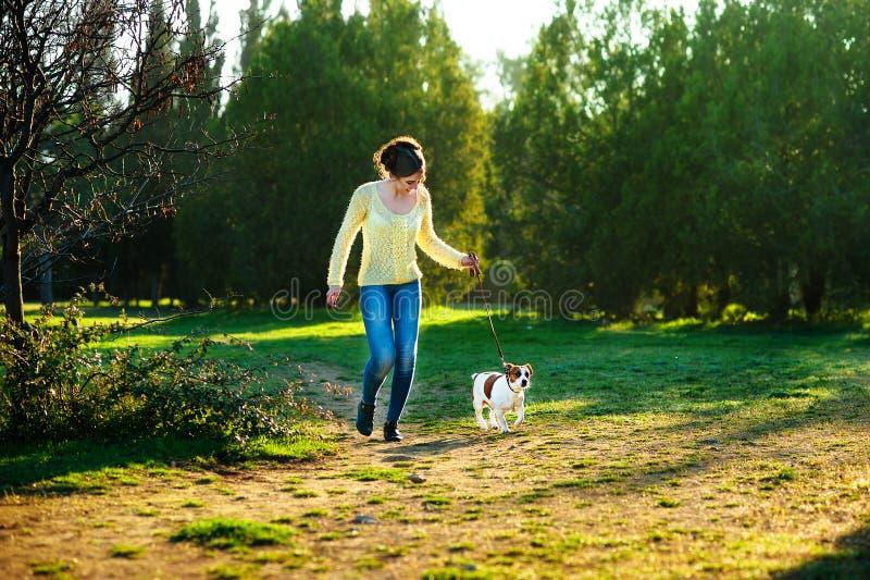 Lycklig ung kvinna som joggar med hennes Jack Russell terrierhund royaltyfri bild