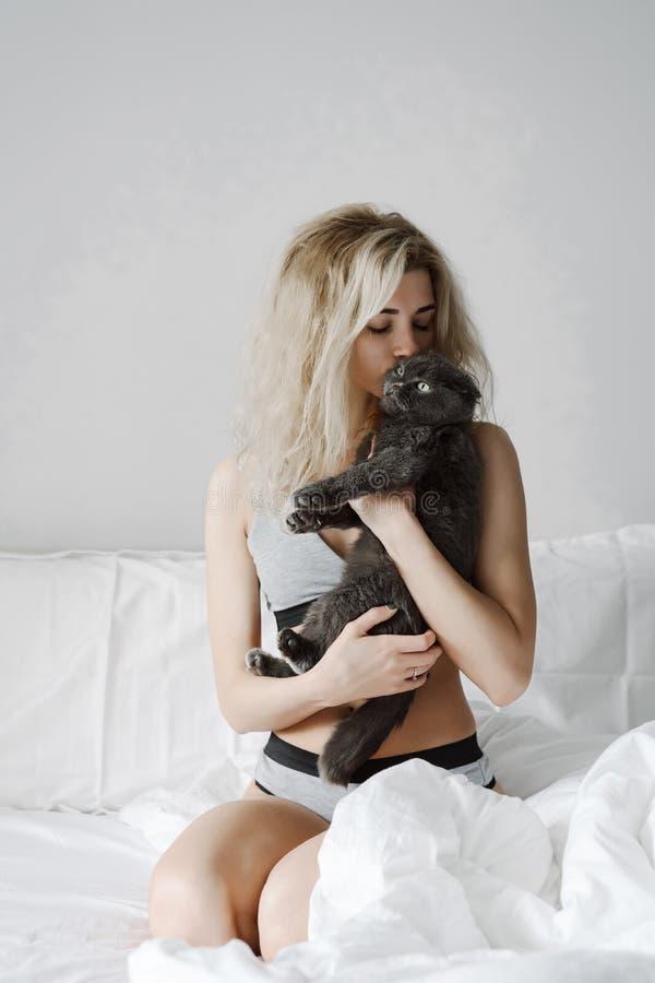 Lycklig ung kvinna som kramar en katt royaltyfria foton