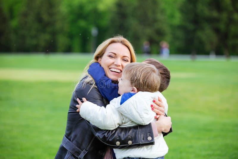 Lycklig ung kvinna som kramar två söner och skratta arkivbild
