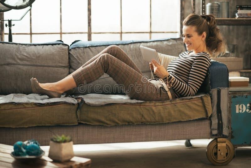 Lycklig ung kvinna som lägger på soffan och använder minnestavlan royaltyfria foton