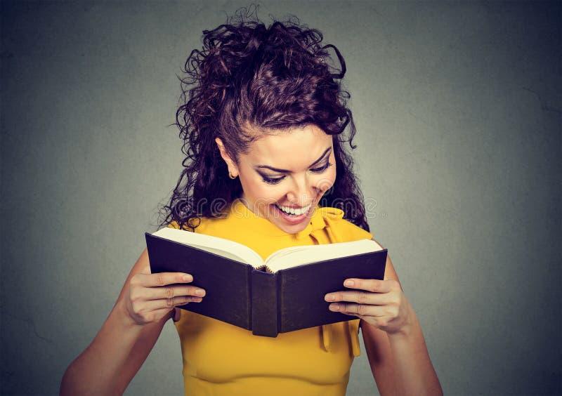 Lycklig ung kvinna som läser en bok royaltyfri fotografi