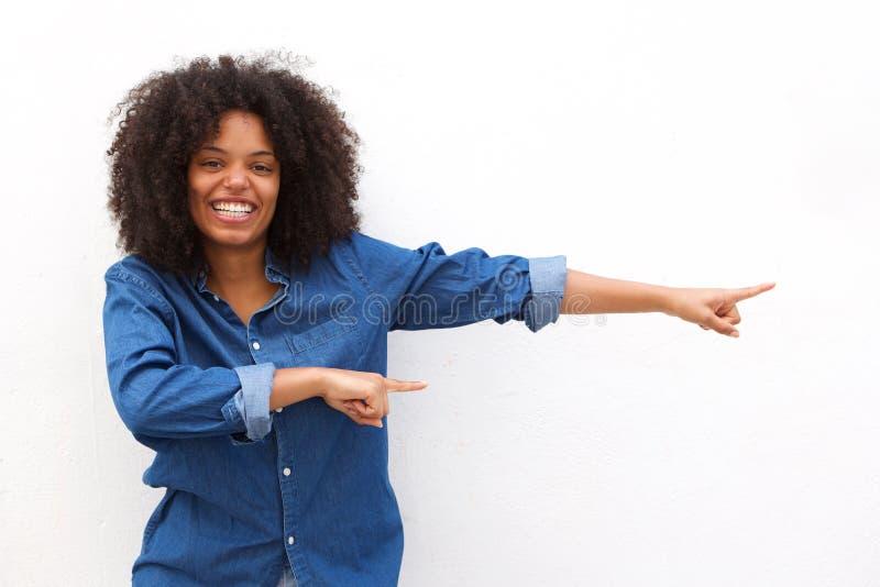 Lycklig ung kvinna som ler och pekar mot vit bakgrund arkivfoto