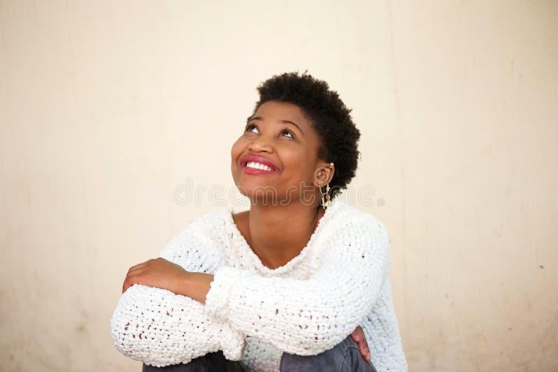 Lycklig ung kvinna som ler och ser upp royaltyfri foto