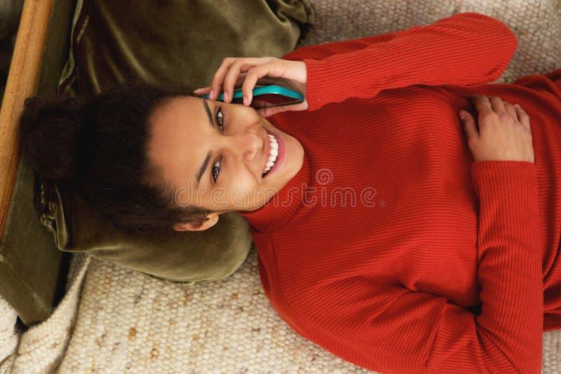 Lycklig ung kvinna som ligger på soffan och talar på mobiltelefonen royaltyfri bild