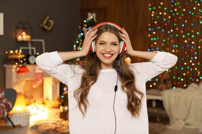 Lycklig ung kvinna som lyssnar till julmusik royaltyfria bilder