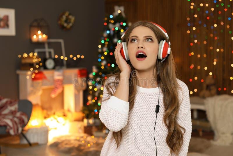 Lycklig ung kvinna som lyssnar till julmusik royaltyfri bild