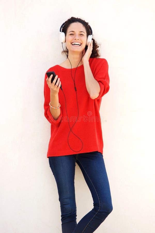 Lycklig ung kvinna som lyssnar till musik med hörlurar arkivfoton