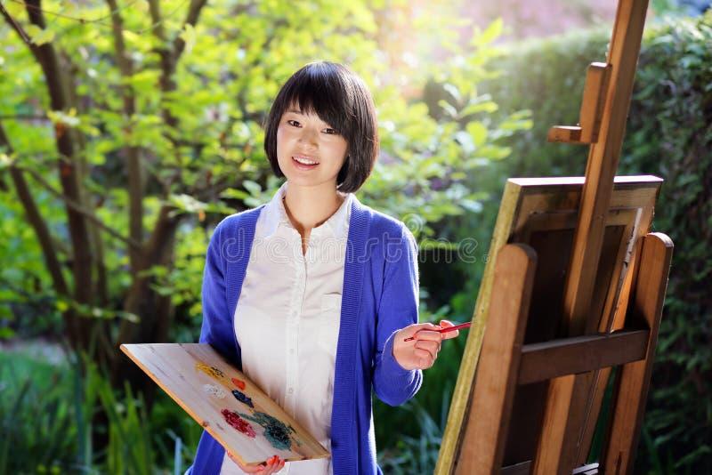 Lycklig ung kvinna som målar en kanfas i trädgården arkivfoto