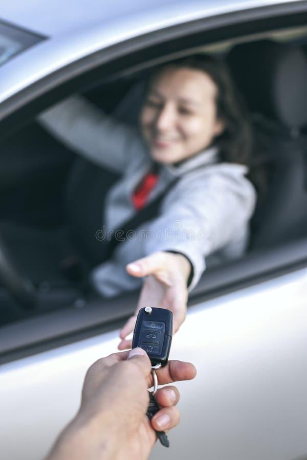 Lycklig ung kvinna som mottar tangenterna av hennes nya bil royaltyfria bilder