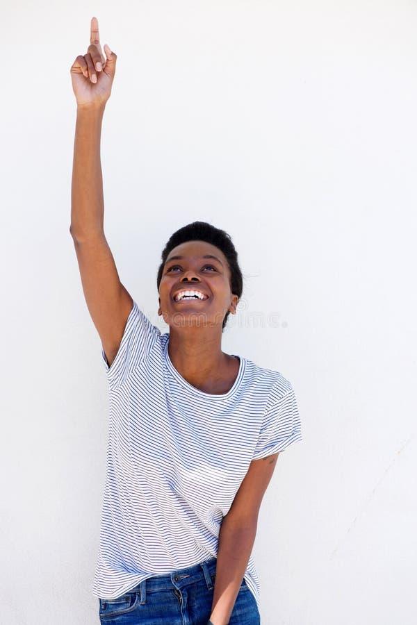 Lycklig ung kvinna som pekar upp fingret royaltyfria foton