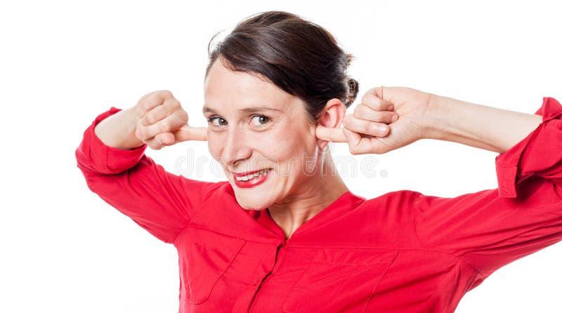 Lycklig ung kvinna som pluggar öron för att ignorera problem arkivbilder