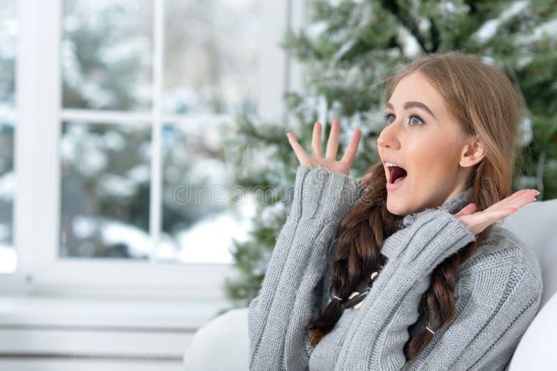 Lycklig ung kvinna som poserar nära julgranen arkivfoto