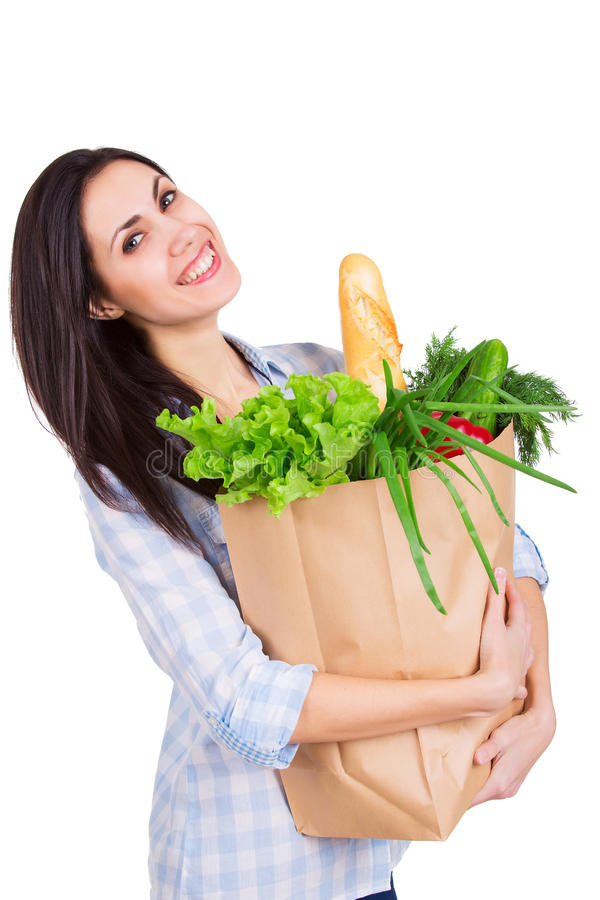 Lycklig ung kvinna som rymmer den pappers- påsen med livsmedel arkivfoton