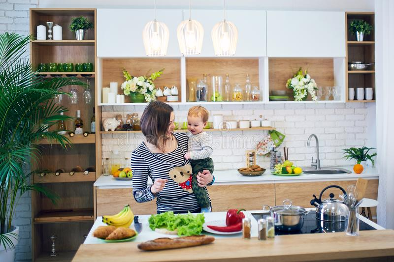 Lycklig ung kvinna som rymmer ett 1 årigt barn och tillsammans lagar mat i köket fotografering för bildbyråer