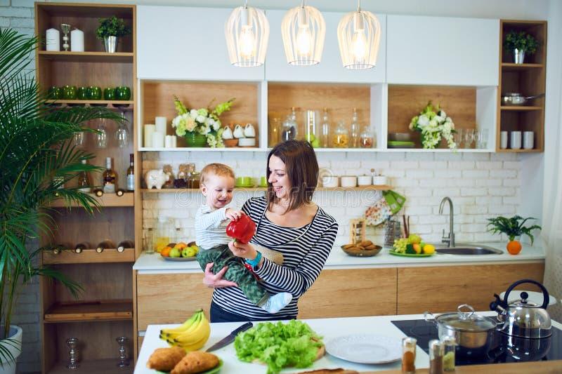 Lycklig ung kvinna som rymmer ett 1 årigt barn och tillsammans lagar mat i köket royaltyfria foton