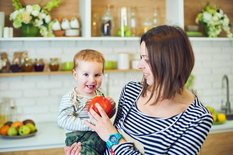 Lycklig ung kvinna som rymmer ett 1 årigt barn och tillsammans lagar mat i köket arkivbild