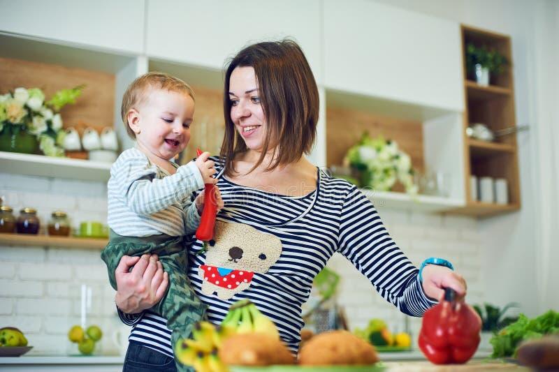Lycklig ung kvinna som rymmer ett 1 årigt barn och tillsammans lagar mat i köket arkivbilder