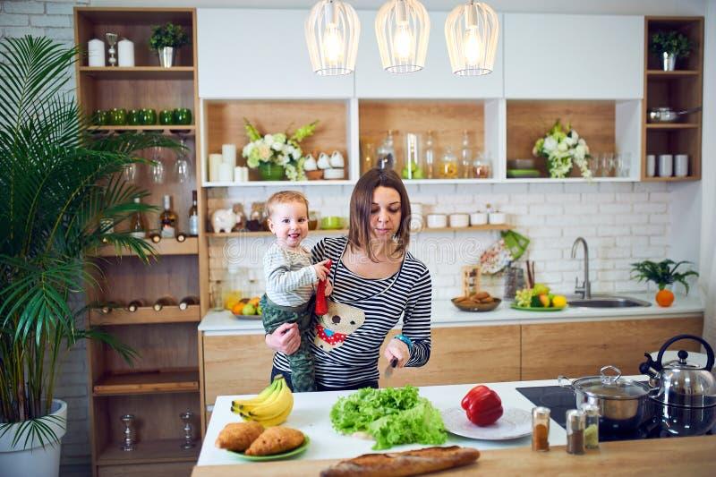 Lycklig ung kvinna som rymmer ett 1 årigt barn och tillsammans lagar mat i köket royaltyfri bild