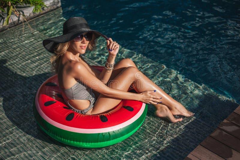 lycklig ung kvinna som sitter i uppblåsbar cirkel på poolsiden royaltyfri bild