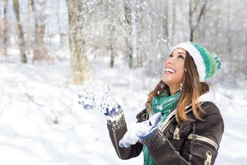 Lycklig ung kvinna som spelar i snön royaltyfri foto