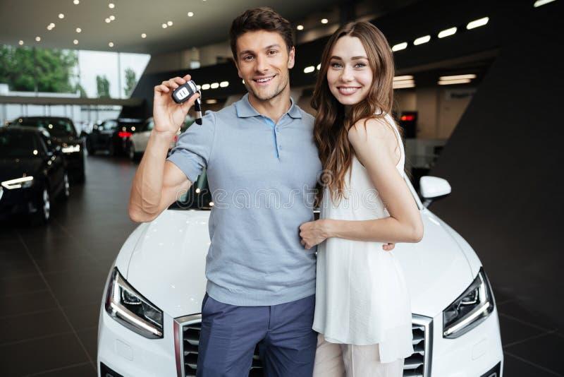 Lycklig ung kvinna som står den near bilen med pojkvännen royaltyfri bild
