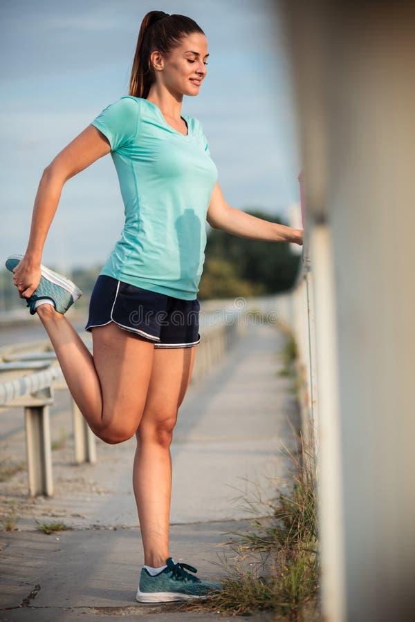 Lycklig ung kvinna som sträcker ben efter en hård utomhus- stads- genomkörare royaltyfria bilder