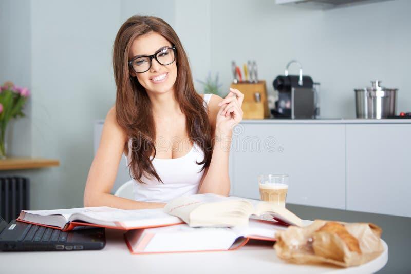 Lycklig ung kvinna som studerar i kök royaltyfria bilder