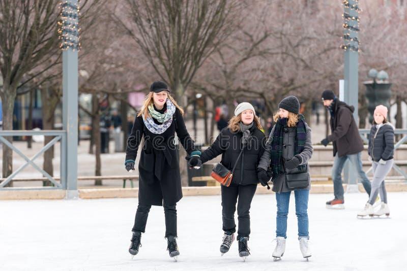 Lycklig ung kvinna som tre utomhus åker skridskor på en offentlig skridskoåkningisbana arkivbilder
