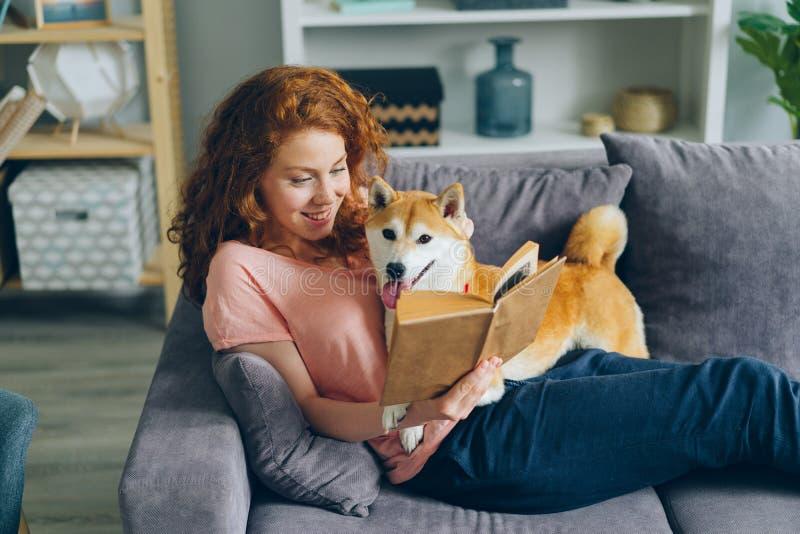 Lycklig ung kvinna som tycker om boken och slår den gulliga vovven som sitter på soffan i lägenhet royaltyfri fotografi