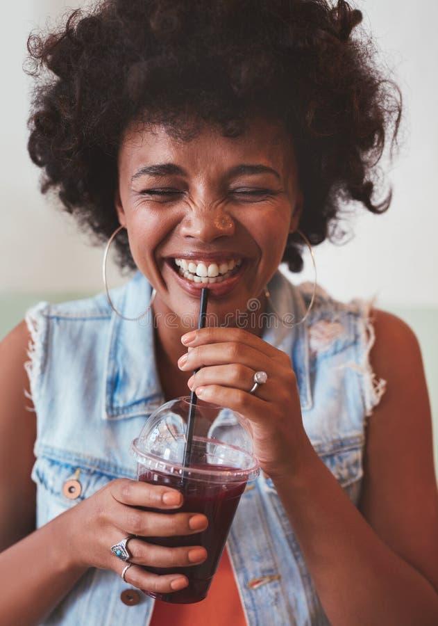 Lycklig ung kvinna som tycker om fruktsaft för ny frukt fotografering för bildbyråer