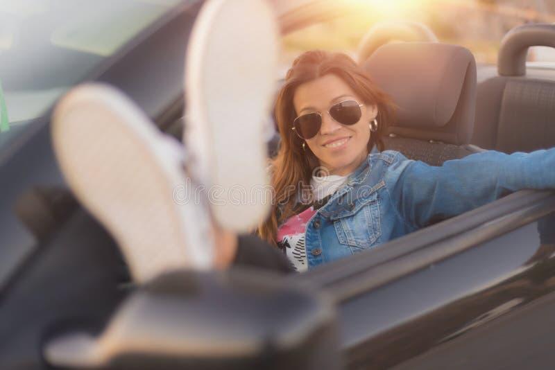 Lycklig ung kvinna som tycker om hennes konvertibla bil arkivfoto
