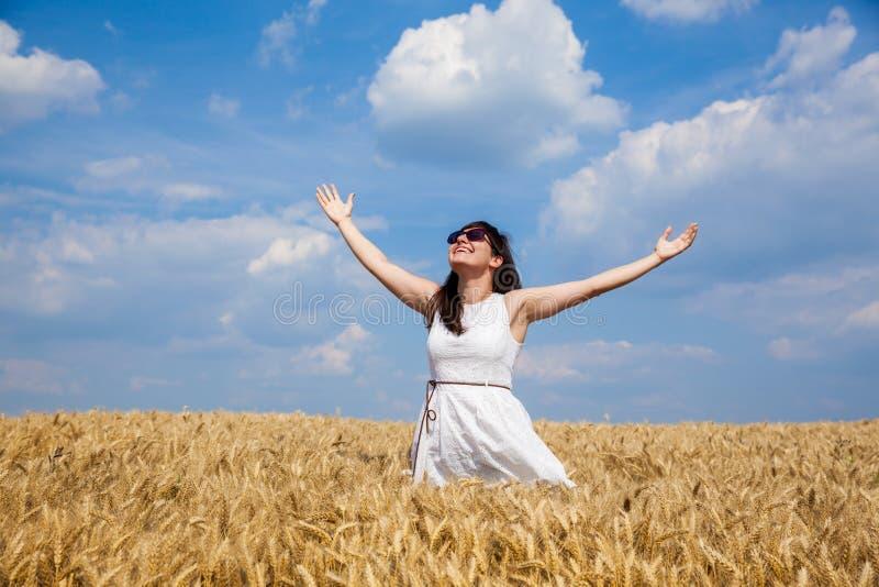 Lycklig ung kvinna som tycker om liv i guld- vetefält arkivfoton