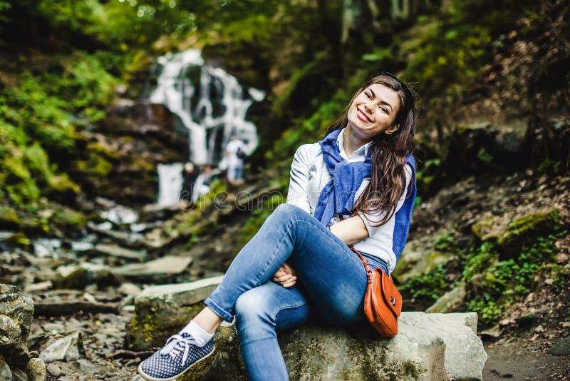 Lycklig ung kvinna som tycker om naturen med vattenfallet i bakgrund fotografering för bildbyråer