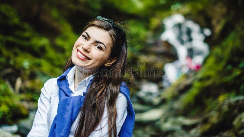 Lycklig ung kvinna som tycker om naturen med vattenfallet i bakgrund royaltyfri foto