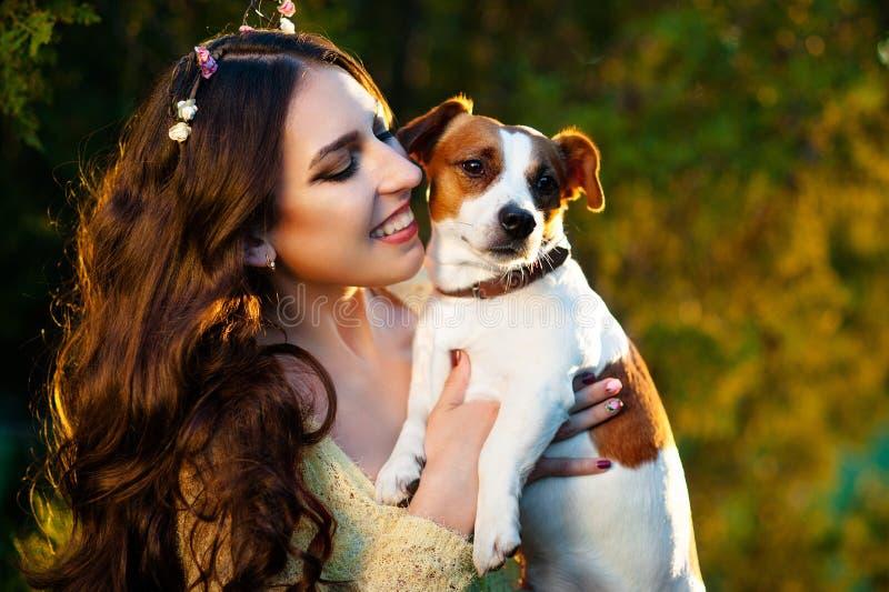 Lycklig ung kvinna som utomhus kramar och har gyckel med hennes Jack Russell Terrier arkivfoto