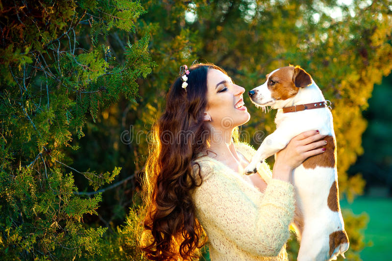 Lycklig ung kvinna som utomhus kramar och har gyckel med hennes Jack Russell Terrier fotografering för bildbyråer