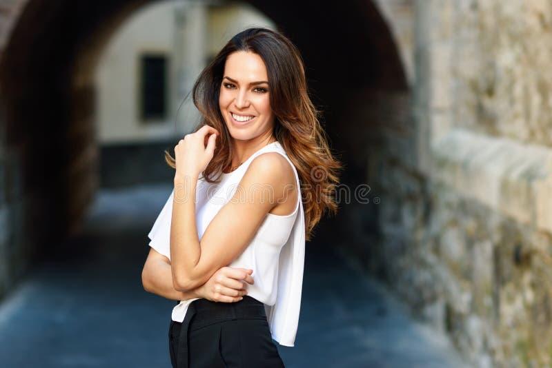 Lycklig ung kvinna som utomhus ler till kameran arkivbild