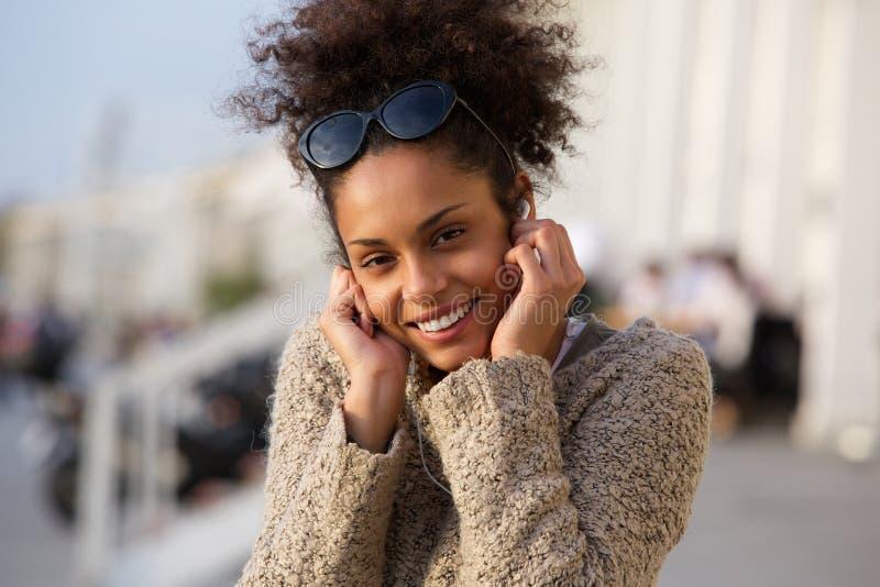 Lycklig ung kvinna som utomhus lyssnar till musik på hörlurar royaltyfria bilder