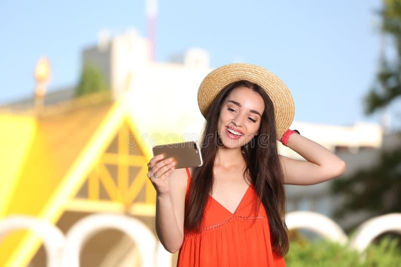 Lycklig ung kvinna som utomhus tar selfie på soligt arkivbild