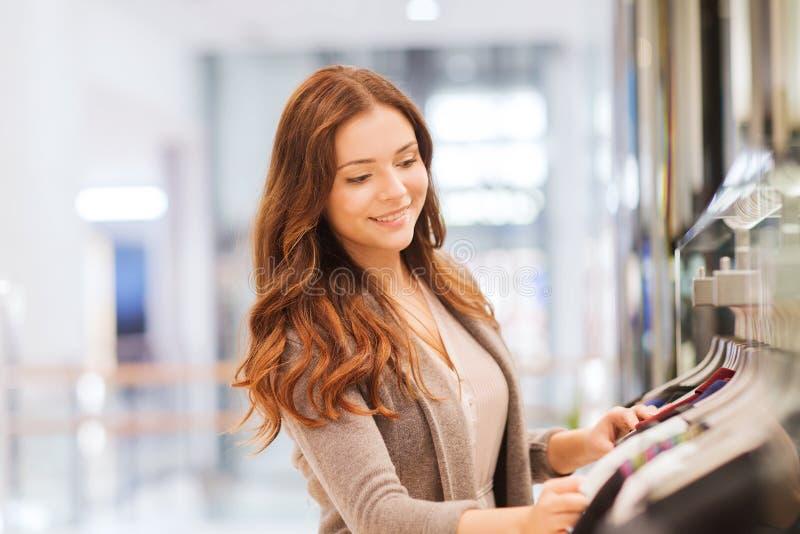 Lycklig ung kvinna som väljer kläder i galleria arkivfoton