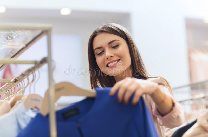 Lycklig ung kvinna som väljer kläder i galleria royaltyfri fotografi